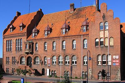Obraz przedstawia budynek z czerwonej cegły